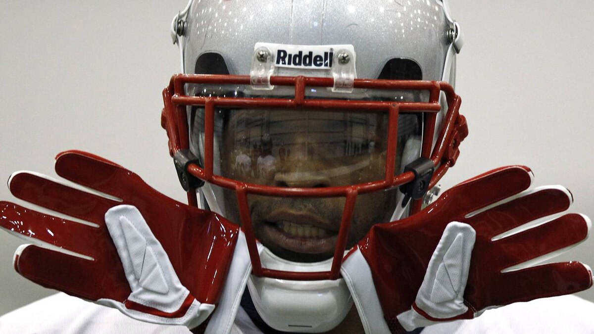 New England Patriots' running back BenJarvus Green-Ellis runs with his gloves stuck in his face mask during a practice for the NFL Super Bowl XLVI in Indianapolis. The New York Giants will play the New England Patriots in the Super Bowl on February 5. REUTERS/Jim Young