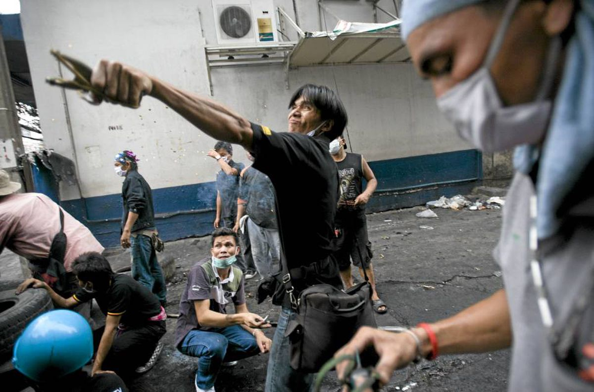 An anti-government Red Shirt protester launches a slingshot loaded with a large firecracker toward Thai soldiers as clashes continued in Bangkok on Monday.