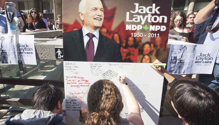 A crowd gathers and people line up to sign a giant card for Jack Layton's family during an impromptu memoria at City Hall in Toronto.