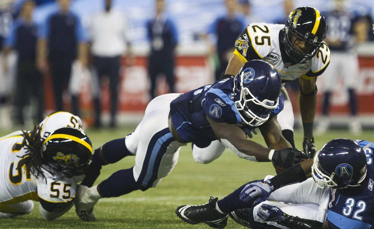 Toronto Argonauts Cory Boyd (C) runs the ball in for a touchdown with teammate Andre Durie (R) past Hamilton Tiger-Cats Markeith Knowlton and Stevie Baggs (L) during the second half of their CFL football in Toronto, November 3, 2011.