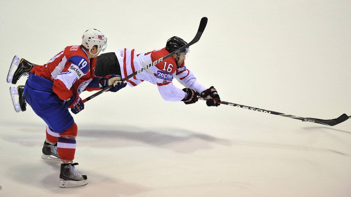 Canada's Andrew Ladd dives after a puck followed by Norway's Per-Age Skroder during their IIHF Ice Hockey World Championship group F qualification match in Kosice city on May 7, 2011.