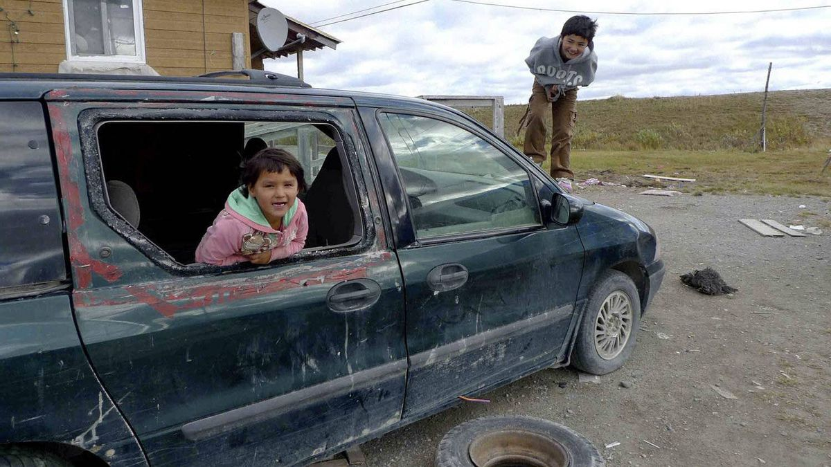 Children play on a beat-up old minivan in Kashechewan, where most of the residents are on welfare and the birth rate is triple the national average.