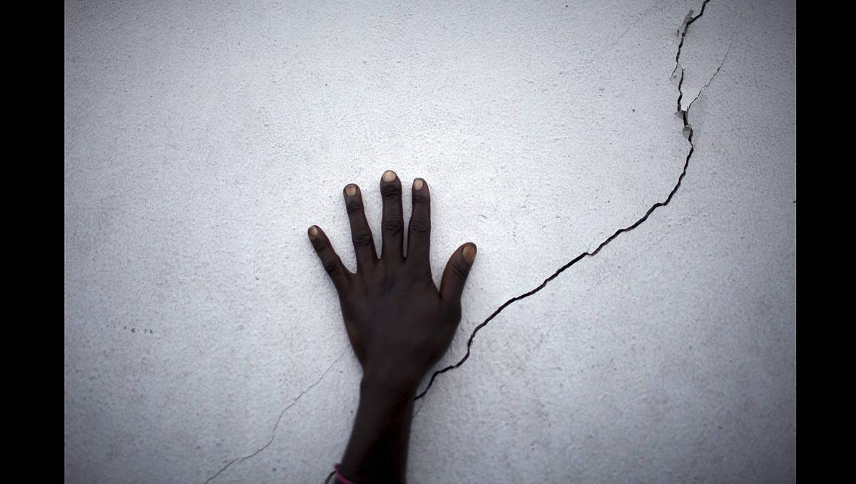 A woman puts her hand near a crack on a wall as she waits for food distribution in Port-au-Prince Haiti January 27, 2010.