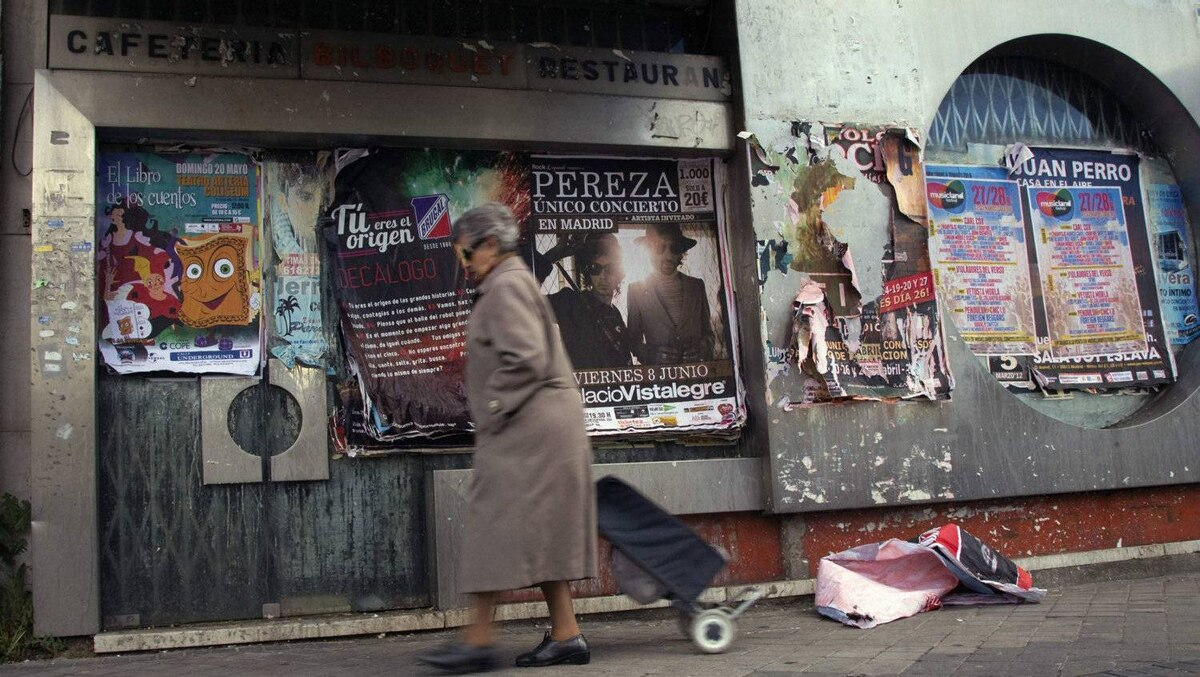 A woman pulls her shopping trolley a she walks past a closed down restaurant filled with publicity posters in Madrid.