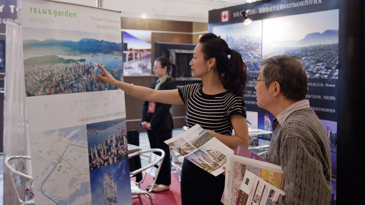Angela Li, left, shows a picture of Vancouver to a visitor at the booth of Westbank Corp. in Shanghai, May 2, 2012.