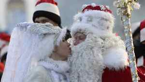 """A man dressed as Father Frost, the local equivalent of Santa Claus, receives a kiss from his """"granddaughter"""" Snegurochka (Snow Maiden) during a New Year's Day parade in Bishkek December 31, 2011."""