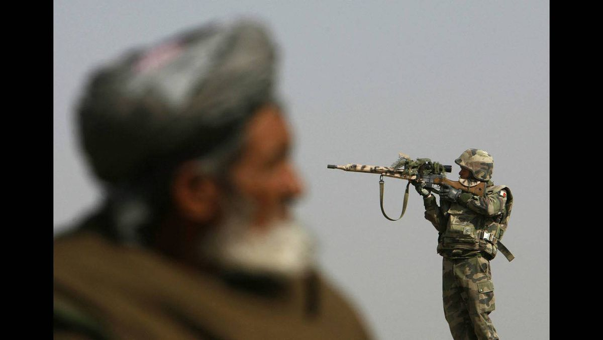 A French sniper (R) looks through his rifle's scope while keeping watch over Qarabagh district, about 40 km north of Kabul, November 20, 2007.
