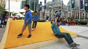 Marcel Graf plays with his 15-month-old son, Leon, at the Picnurbia installation in Robson Square in Vancouver, Aug. 10, 2011. Picnurbia, a pop up picnic zone between Robson Square and the Vancouver Art Gallery, has bright yellow artificial turf, grassy hills, beach umbrellas and built-in benches.