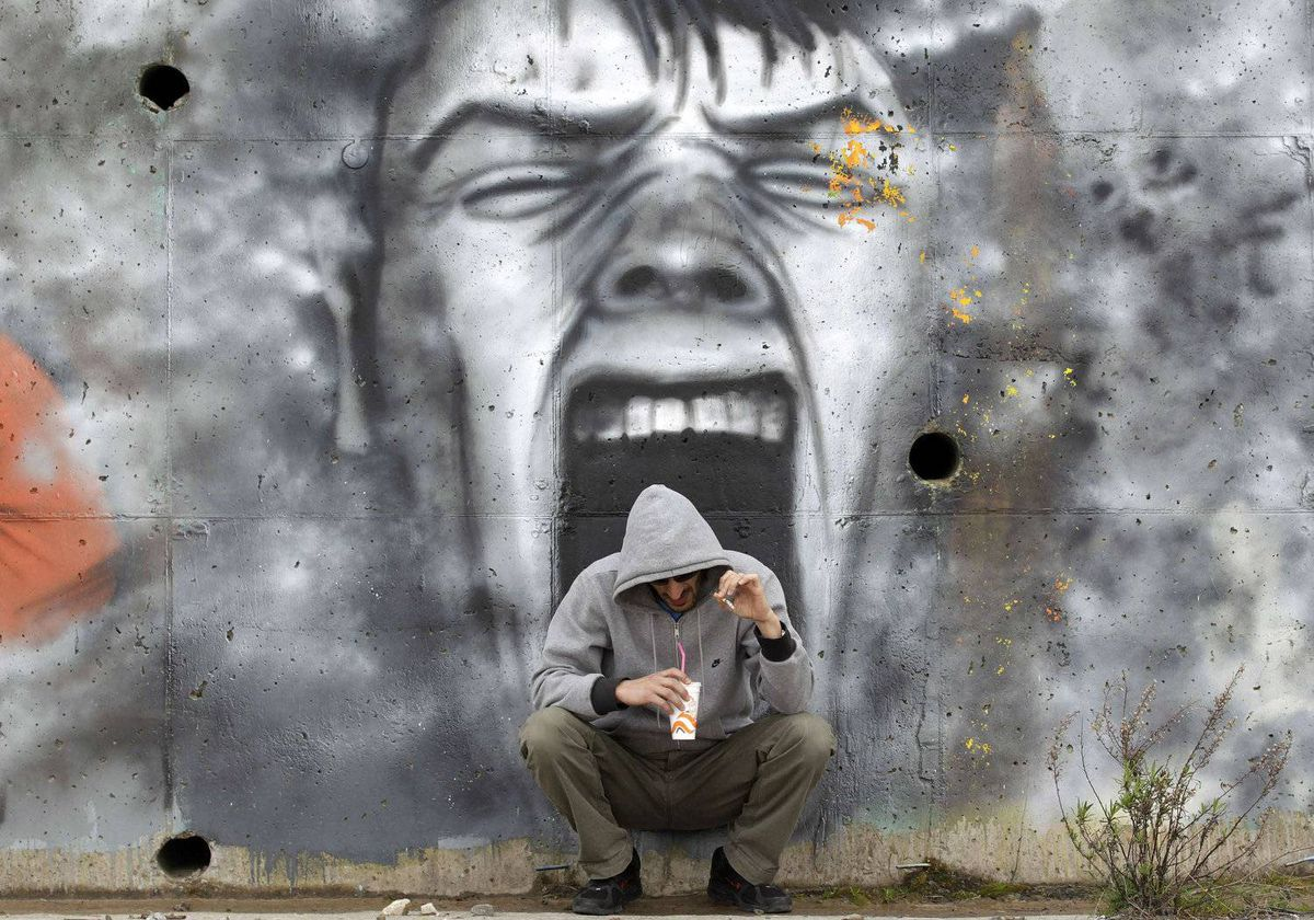 A man drinks coffee in front of a mural near the coastal town of Kalamatta in the Messinia area of Greece March 23, 2012.