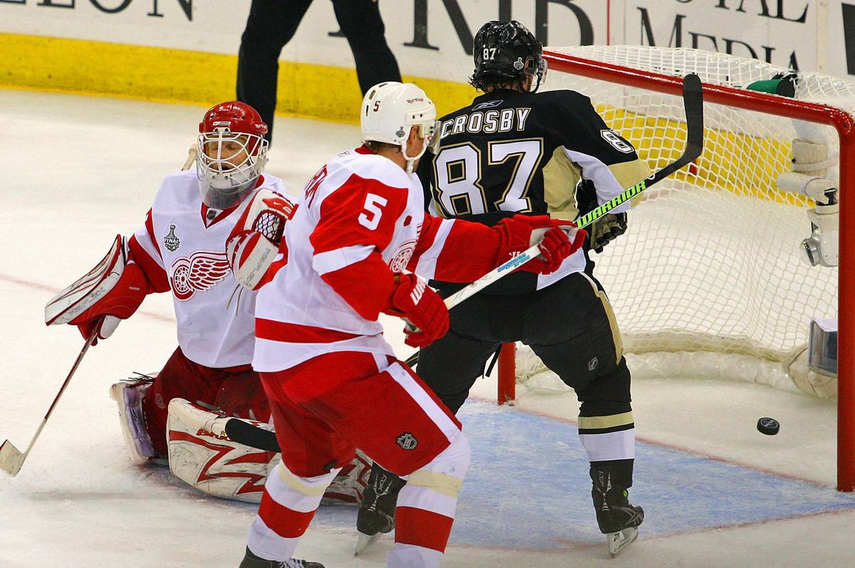 Goaltender Chris Osgood of the Detroit Red Wings reacts as Nicklas Lidstrom and Sidney Crosby of the Pittsburgh Penguins watch the go-ahead goal scored by Sergei Gonchar.
