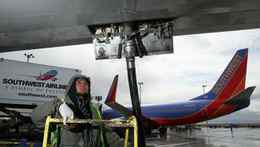 A Swissport employee Christopher Gonzalez monitors a fuel line as he refuels a Southwest Airlines plane at the Oakland International Airport.