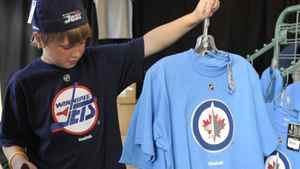 Winnipeg Jets fan Matthew Sawka holds a t-shirt with the NHL team's new logo in Winnipeg, July 22, 2011. REUTERS/Fred Greenslade