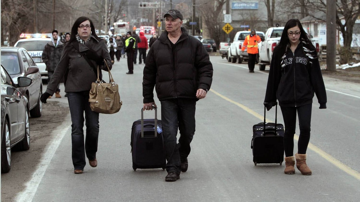 Deanna Villella, left, a passenger on the derailed Via train in Burlington, leaves the scene of the crash along with her husband Roger Collins and daughter Jasmine who came from Welland to pick her up.