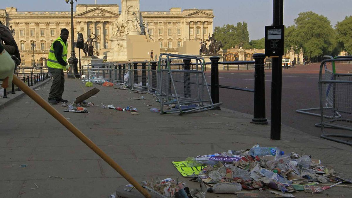 Cleaners sweep up rubbish left the previous night by revelers outside Buckingham Palace.