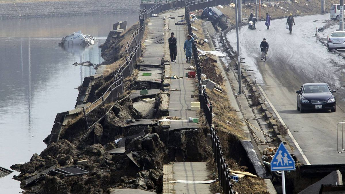 People make their way along on a damaged river bank following a massive tsunami that's triggered by a catastrophic earthquake in Tagajo near Sendai, northeastern Japan, on Sunday, March 13, 2011.