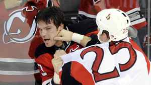 Ottawa Senators winger Chris Neil (R) lands a punch on New Jersey Devils winger David Clarkson as a fan reacts as they fight in the first period of their NHL hockey game in Newark, New Jersey, January 4, 2009.