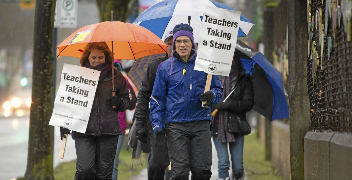 Teachers walk an information picket line at Sir Guy Carleton school in Vancouver Monday.