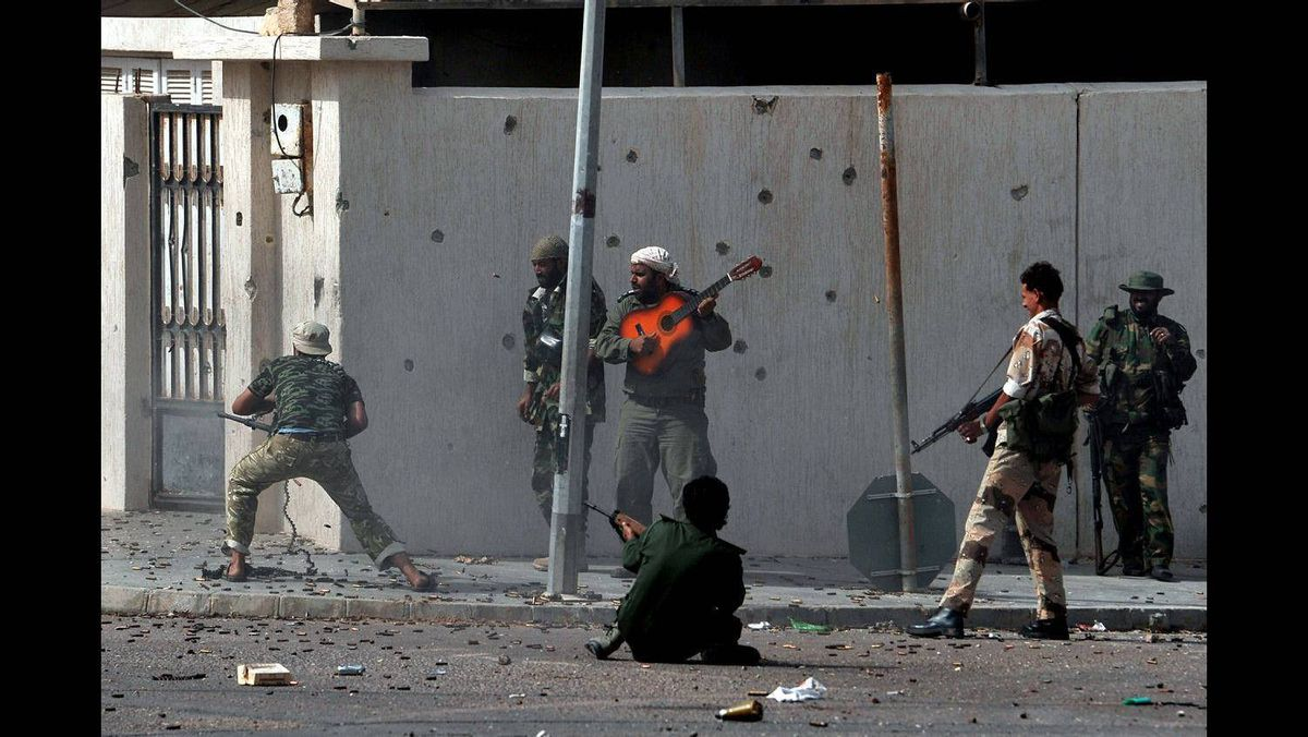 National Transitional Council fighters fire against Moamer Kadhafi's troops in the town of Sirte on October 10, 2011, as they move in for the kill against the strongman's remaining diehards.