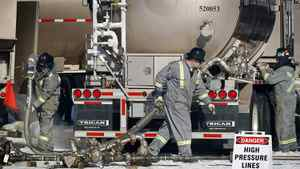 Workers connect liquid nitrogen storage tanks at a hydraulic fracturing operation near Bowden, Alta., on Feb. 14, 2012.