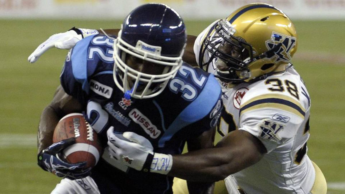 Toronto Argonauts running back Andre Durie is tackled by Winnipeg Blue Bombers linebacker Marcellus Bowman