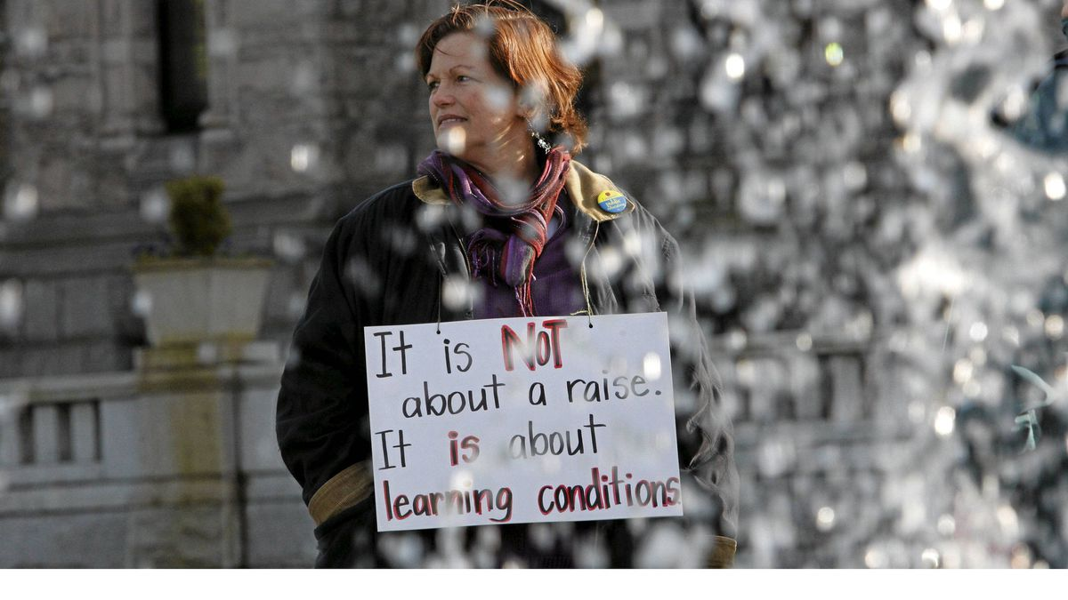 A woman carries a sign during a rally for B.C. teachers in front of the Legislature building in Victoria on Monday.