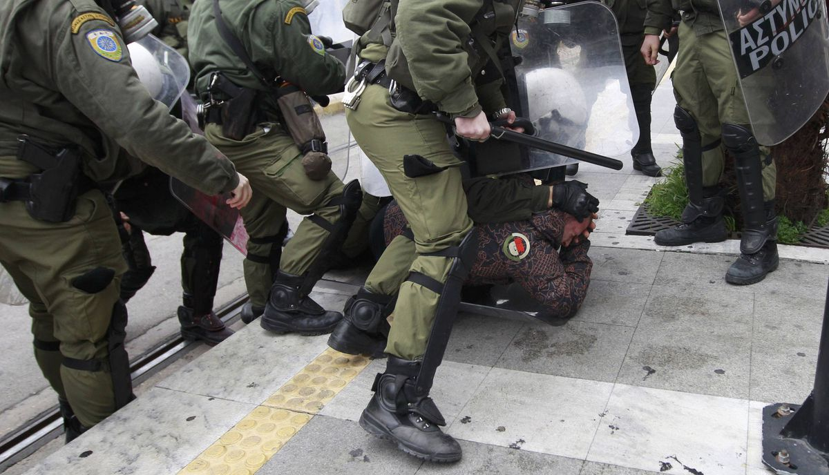 A demonstrator is detained by riot police during protests against planned reforms by Greece's coalition government in Athens, February 10, 2012.