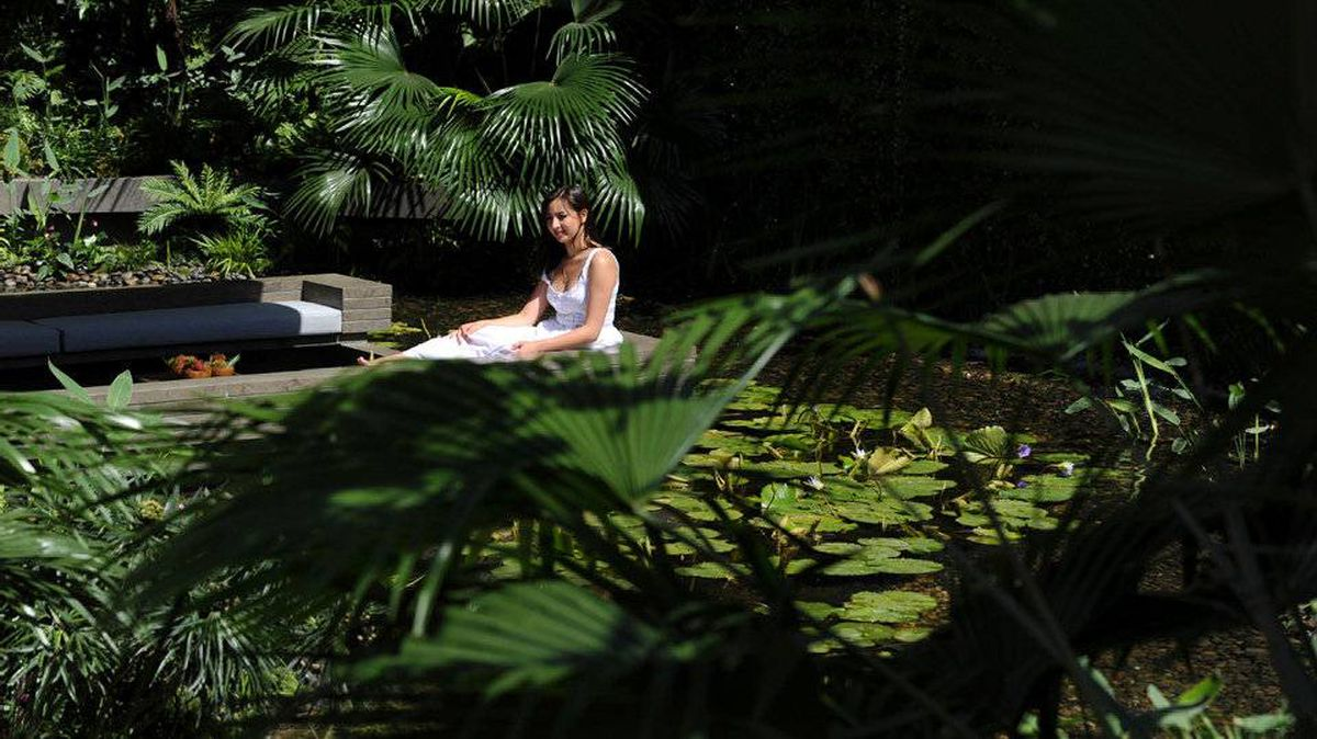 A model poses for photographers in the Tourism Malaysia Garden during the Chelsea Flower Show in London, on May 23, 2011.