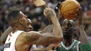 Boston Celtics' forward Kevin Garnett (R) looks to pass against Toronto Raptors' defenders James Johnson (front L) and Ed Davis during the first half of their NBA basketball game in Toronto April 13, 2012. REUTERS/Mike Cassese