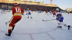 Calgary Flames' alumni Gary Roberts (L) handles the puck while Montreal Canadiens' alumni Mike Lalor chases him during the second period of their the NHL Heritage Classic alumni hockey game in Calgary, Alberta, February 19, 2011. The two teams played each other in the 1989 Stanley Cup final when the Flames defeated the Canadiens to win the Stanley Cup. REUTERS/Todd Korol