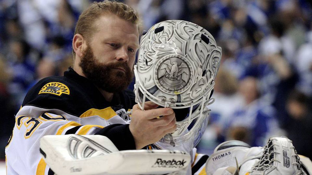 Tim Thomas of the Boston Bruins puts on his mask prior to the start of Game 7.