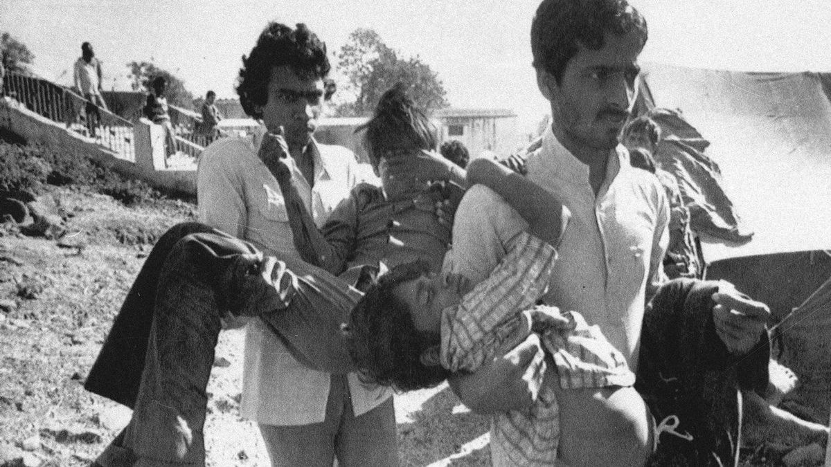 In this Dec. 5, 1984 file photo, two men carry children blinded by the Union Carbide chemical pesticide leak to a hospital in Bhopal, India. The tragedy left an estimated 15,000 people dead. AP Photo/Sondeep Shankar, File
