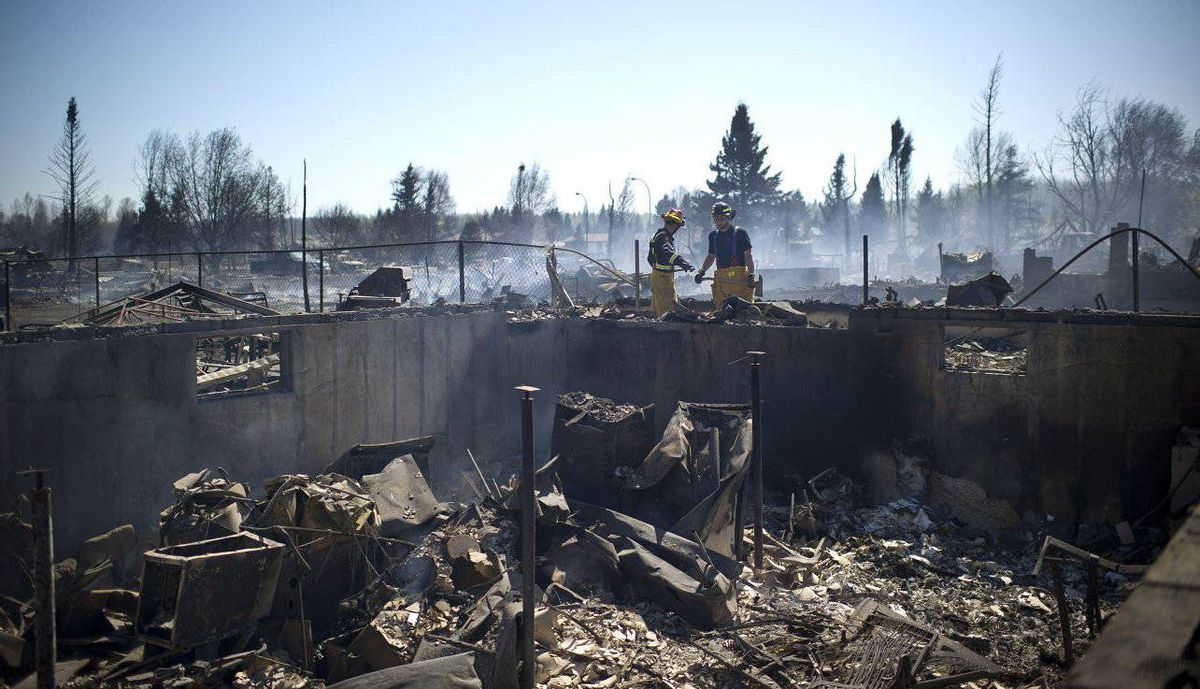Firefighters look over the remains of a house in Slave Lake Alberta after a massive forest fire stoked by strong winds burnt through the community.