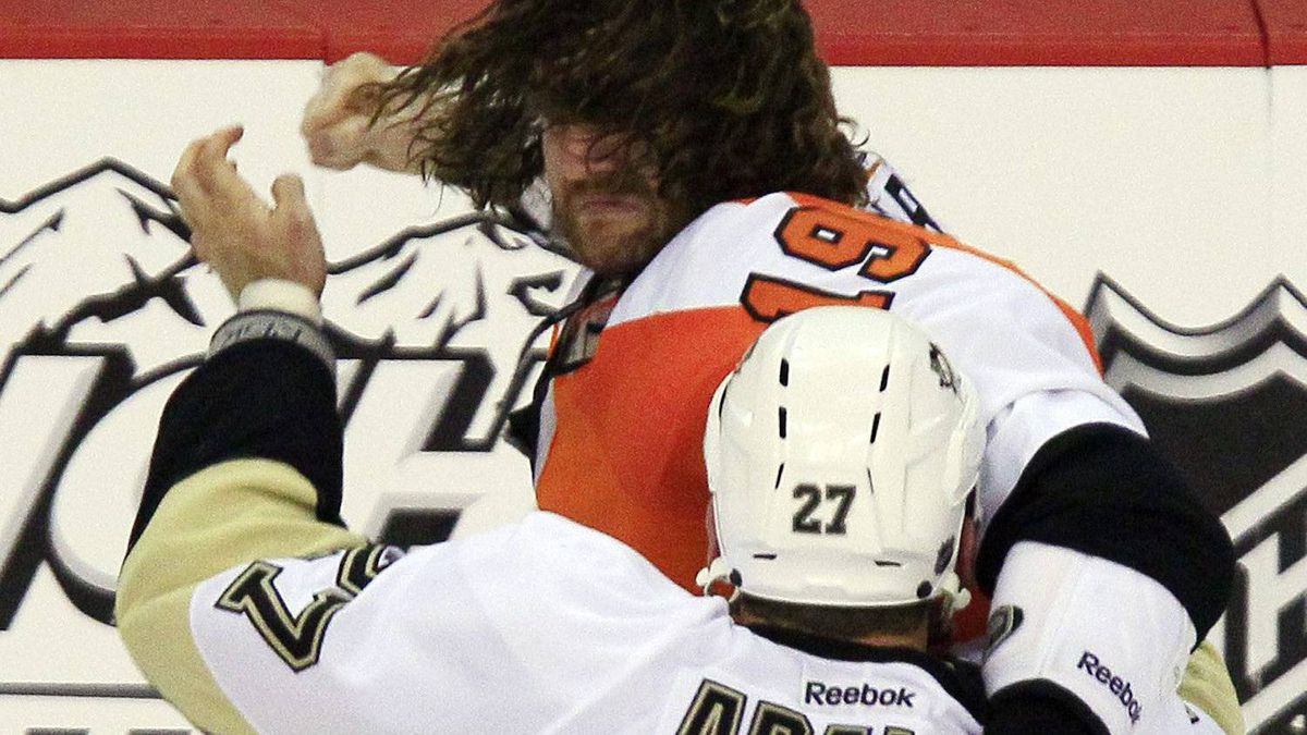 Philadelphia Flyers Scott Hartnell, hair flying, winds up a punch as he and Pittsburgh Penguins Craig Adams battle during one of several simultaneous fights going on in the third period of Game 3 in a first-round NHL Stanley Cup playoffs hockey series, Sunday, April 15, 2012, in Philadelphia. The Flyers' 8-4 win puts them ahead 3-0 in the series. (AP Photo/Tom Mihalek)