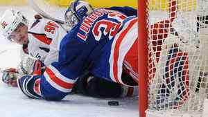 Washington Capitals' Marcus Johansson (L) slides into New York Rangers' goalie Henrik Lundqvist in the second period during Game 1 of their NHL Eastern Conference semi-final playoff hockey game at Madison Square Garden in New York, April 28, 2012. REUTERS/Ray Stubblebine