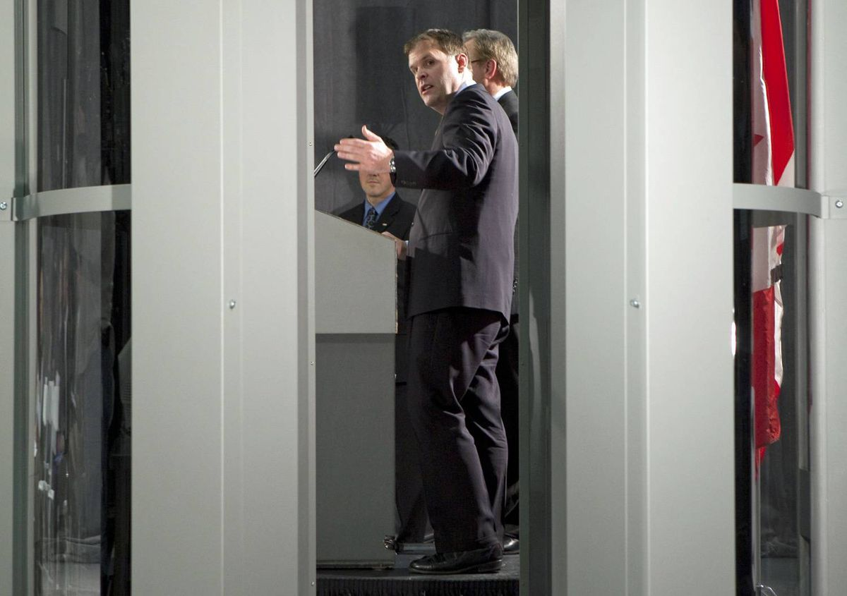 Transport Minister John Baird gestures towards a full body scanner as he announces new airport security measures in Ottawa on Tuesday, Jan. 5, 2010.
