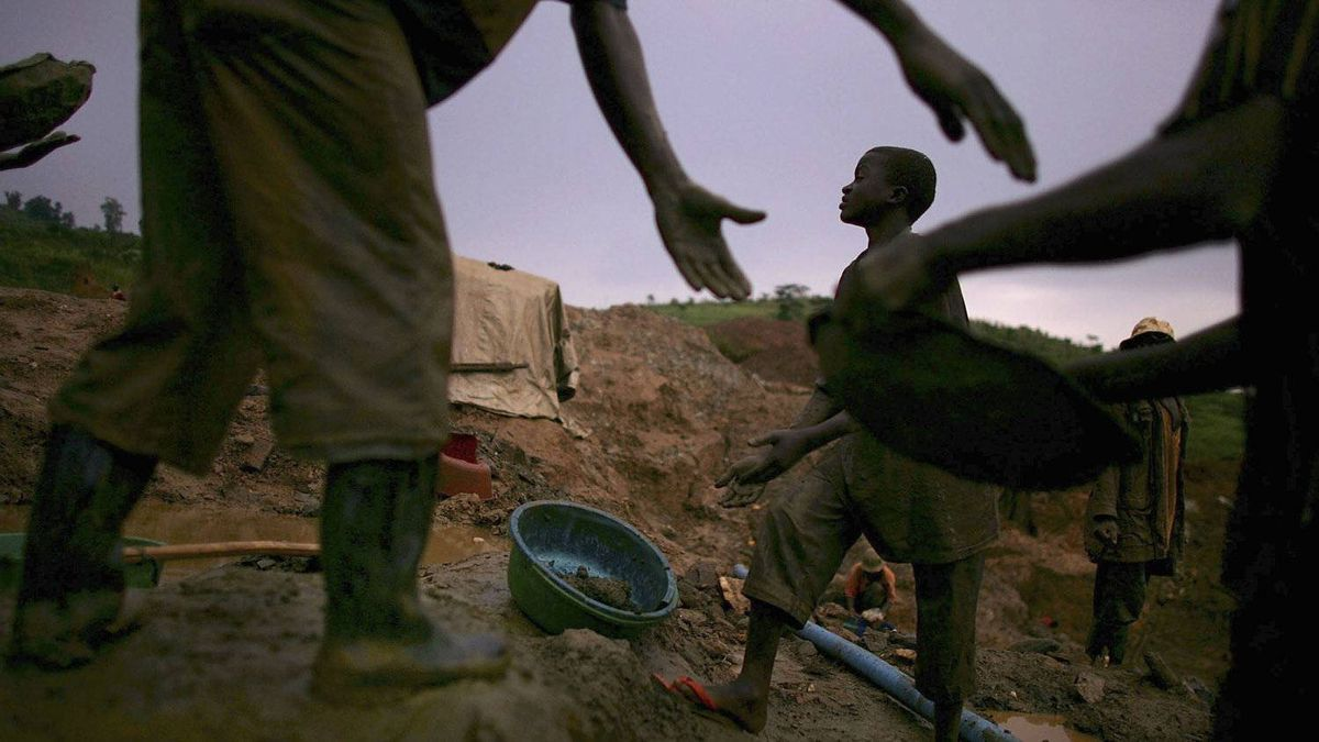 Men pass buckets of dirt which they will sift through while looking for gold March 27, 2006 in Mongbwalu, Congo.