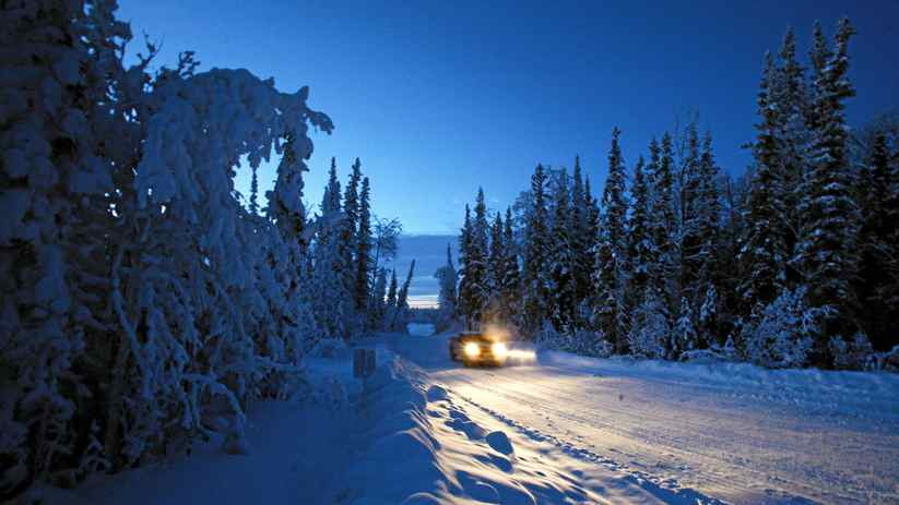 A Ford F150 drives the winter road from Norman Wells to Fort Good Hope, in the early dawn--at about 10:30 in the morning. The road is barely a road at all, in use only during the coldest months of the year. It cuts through otherwise untouched boreal forest, just south of the Arctic Circle, and roughly marks the route of the proposed Mackenzie Valley natural gas pipeline.