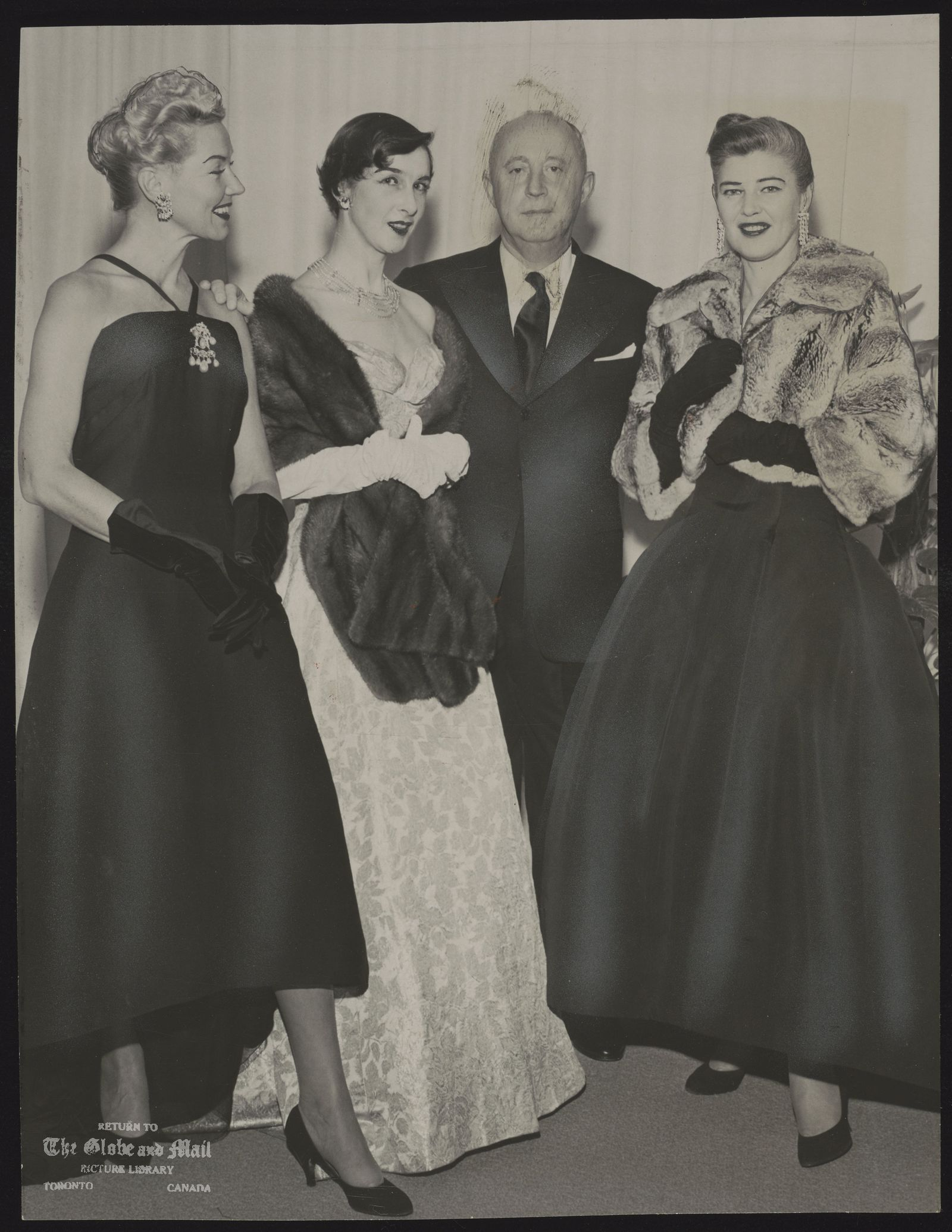 The notes transcribed from the back of this photograph are as follows: Christian Dior poses with three of his models at Holt Renfrew's on Bloor St. Left to right, Mabel Glenby, New York; Jeanne Gora, Paris; and, on the other side of Mr. Dior, Mary Ryan, New York. They flew here especially to model in yesterday's showings.