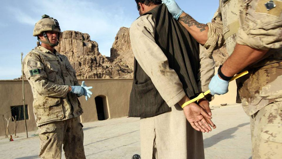 A suspected Taliban prisoner is searched, handcuffed, and processed by members of 1st Princess Patricia's Canadian Light Infantry, after a raid on a compound in Northern Kandahar, 10 May 2006