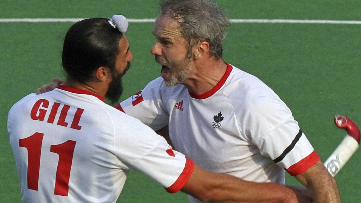 Canada's Rob Short (R) celebrates with teammate Jagdish Gill as Philip Wright (L) watches after a goal against France during their London 2012 Olympic Games men's field hockey qualifying match in New Delhi February 24, 2012. REUTERS/B Mathur