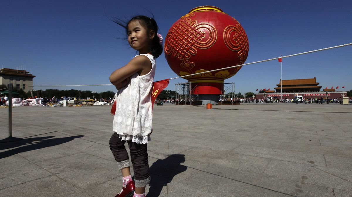A girl poses for a photo in front of a giant red lantern on display at Tiananmen Square for the upcoming National Day celebrations on October 1, in Beijing September 22, 2011.