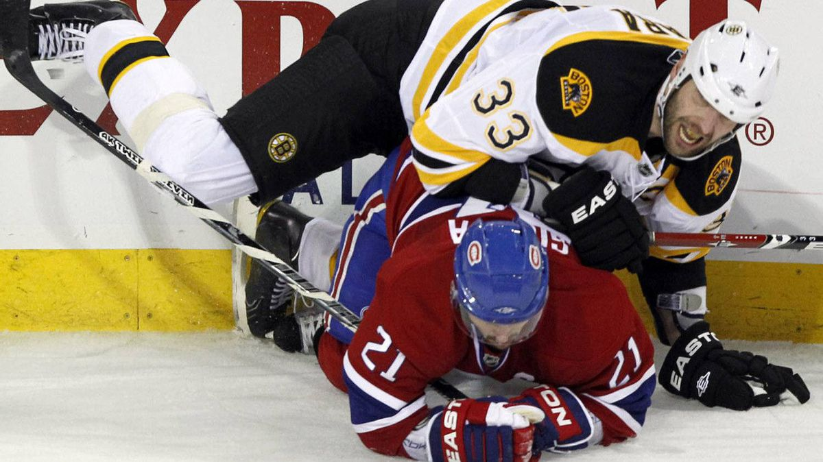 Montreal Canadiens right wing Brian Gionta (21) takes down Boston Bruins defenseman Zdeno Chara (33) during third period of game three NHL Stanley Cup playoff hockey action Monday, April 18, 2011 in Montreal.THE CANADIAN PRESS/Ryan Remiorz