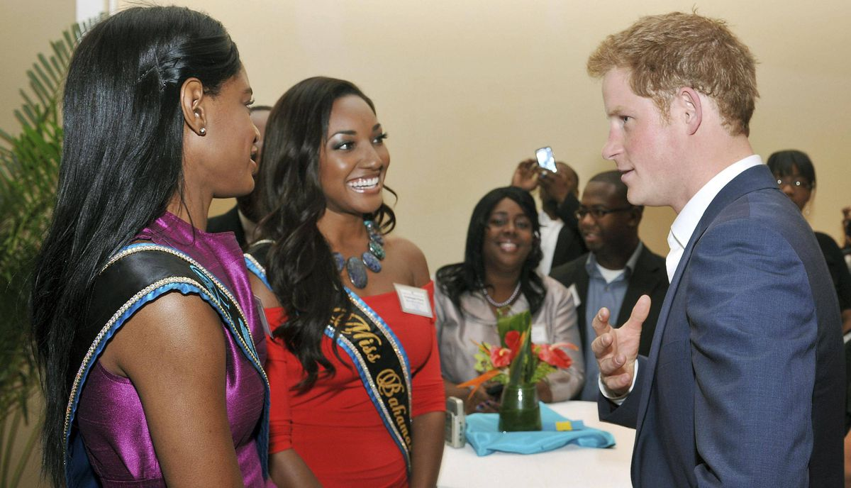 Prince Harry talks with Miss World contestant Sasha Joyce, left, and Miss Bahamas 2011 Anastagia Pierre during a reception in Nassau on March 5, 2012.