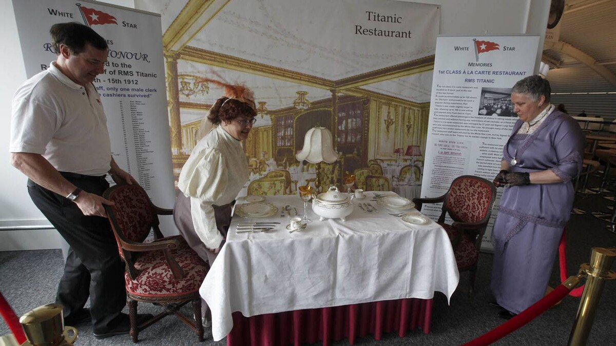 Sisters Terri Williamson, left and Tracie Brelsford from Washington state in the US pose for their photograph as they sit in a mock up of a first class dinning table from the Titanic in the check in area for the MS Balmoral's Titanic memorial cruise in Southampton, England, Sunday, April 8, 2012.
