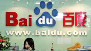 A receptionist works behind the logo for Baidu.com, a Chinese language search engine, at the company's office in Beijing Thursday, July 28, 2005.