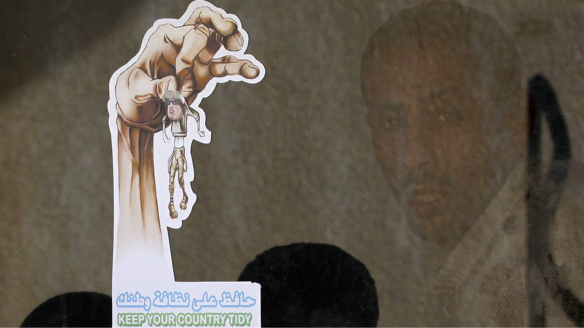 A Libyan citizen stands next to a sticker mocking Moammar Gadhafi as he waits to cross to Egypt in Musaed, Libya, Wednesday, June 8, 2011.
