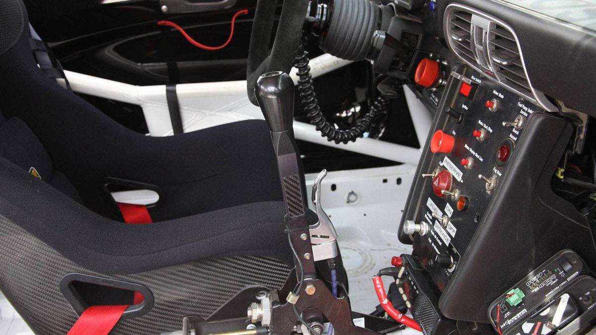 GT3 Cup cars use a long-handled shifter with sequential action. To shift up, the driver pulls the stick backward. Downshifts are made by pushing forward. The silver handle on the front of the stick is a lockout system that prevents first gear and reverse from being engaged by accident.