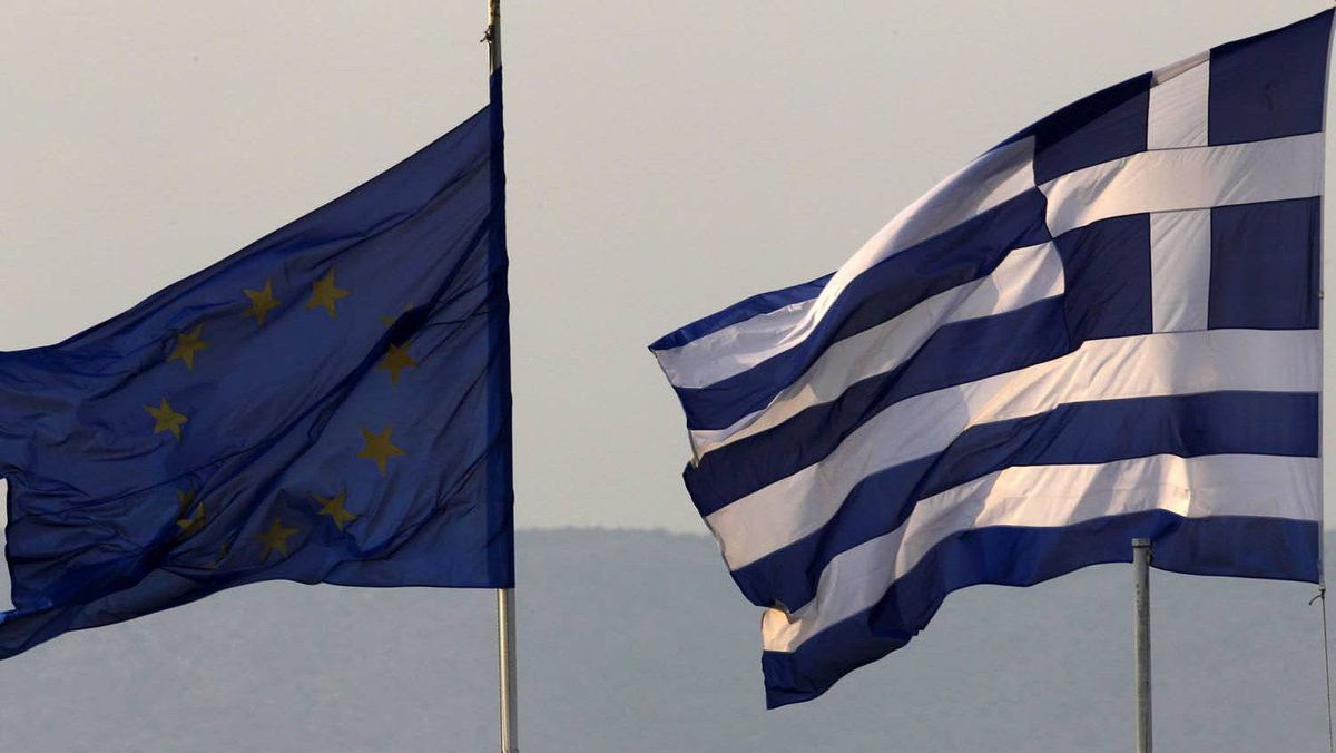 A Greek (R) and an EU flag fly over Greece's Finance Ministry in Athens.