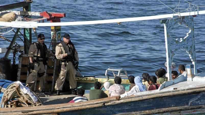 """Two sailors from HMCS Toronto's boarding team keep a watch over the crew of a """"dhow"""" style fishing during a search for evidence connecting them to terrorism. This was HMCS Toronto's first operational vessel inspection of Operation Altair, and found a fully co-operative captain and crew with no improper cargo."""