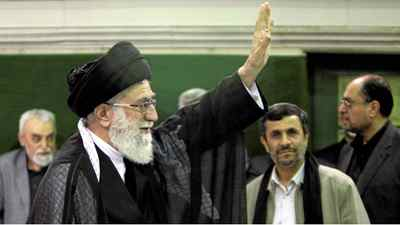 Iranian supreme leader Ayatollah Ali Khamenei, left, waves to his well wishers, unseen, as President Mahmoud Ahmadinejad, second right, looks on, in a religious ceremony, in Tehran, Iran on Saturday, May 7, 2011.